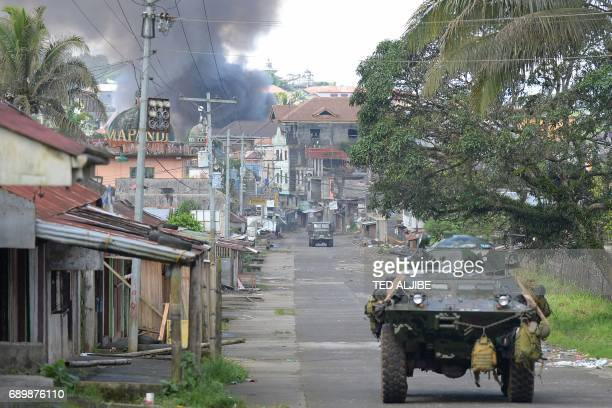 A Philippine Marines truck and armoured personnel carrier speed away as black smoke billows from burning houses after military helicopters fired...