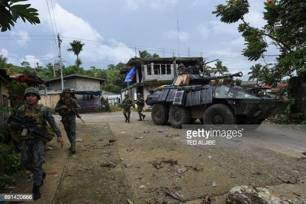 Philippine marines walk next to their V300 light wheeled armoured vehicle after engaging Islamist militants at in Marawi on the southern island of...
