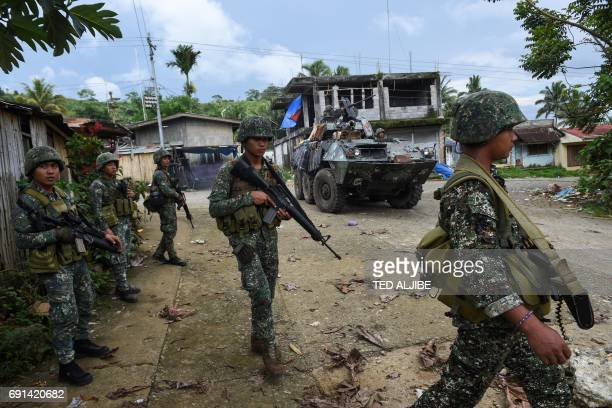 TOPSHOT Philippine marines walk next to their V300 light wheeled armoured vehicle after engaging Islamist militants at in Marawi on the southern...