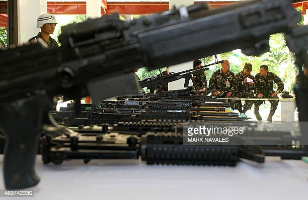 Philippine military personnel sit next to high powered firearms at a military camp in Cotabato in the southern island of Mindanao on February 18...