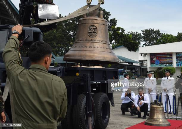 Philippine military personnel unload one of the three Balangiga church bells shortly after it arrived from the US at a military airbase in Manila on...