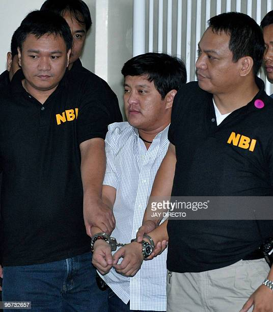 Philippine Muslim politician Andal Ampatuan Jnr is hauled to a Manila court in handcuffs by two National Bureau of Investigation agents in Manila on...