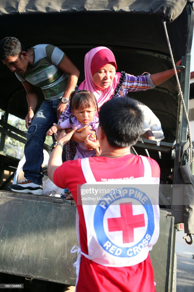 A Philippine National Red Cross worker carries a child displaced by continuing armed conflict between the supporters of Philippine Muslim clan Sulu Sultan Jamalul Kiram III and Royal Malaysian Police in Sabah, Malaysia, as they arrive at Bongao on March 30, 2013 in Bongao, Tawi-Tawi, Philippines. Following the insurgency in Sabah and the Malaysian government's subsequent crackdown on undocumented Filipinos, over 4000 people, mostly Filipino Muslims, have begun evacuating to the southern provinces of Basilan, Sulu, and Tawi-Tawi in the Philippines, with numbers expected to reach more than 100,000.