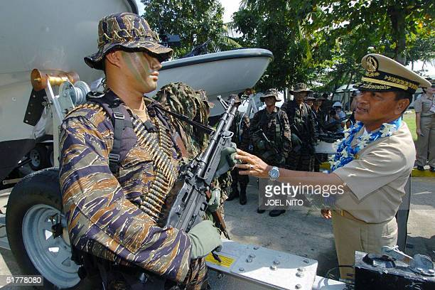 Philippine Navy chief Vice Admiral Ernesto de Leon inspects a new US made machine gun from a navy commando of Naval Special Warfare Group at Sangley...