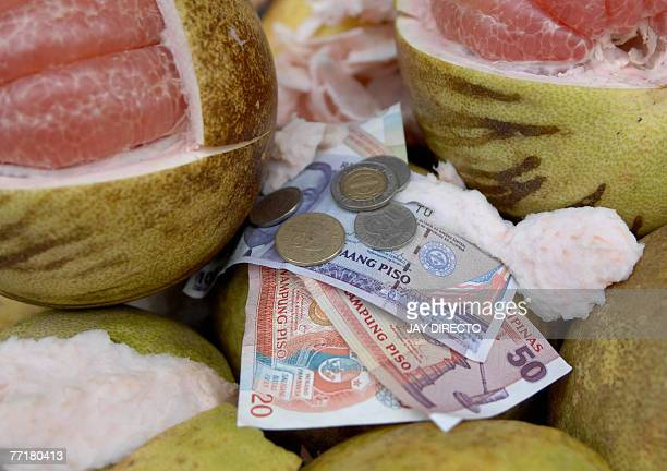 Philippine peso bills and coins are laid on basket as a street vendor peels a fruit in Manila 04 October 2007 The peso was erratic ahead of a key...