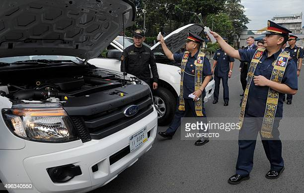 Philippine Police chaplains from the Roman Catholic faith sprinkle holy water as they bless vehicles donated by the US Anti-Terrorism Assistance...