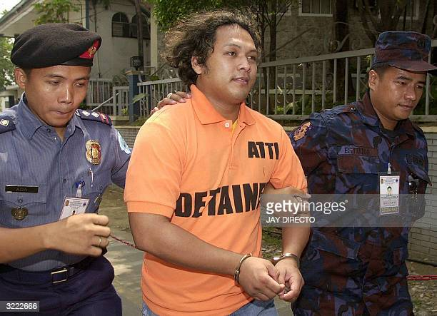 Philippine police escort Abu Sayyaf leader Alhamser Manatad Limbong one of six Muslim Abu Sayyaf guerrillas after they were presentd to the press at...