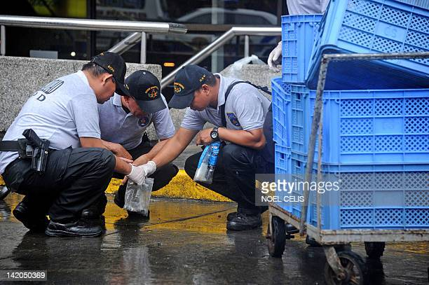 Philippine police investigate the area where a grenade exploded after a daylight robbery outside the upperclass Galleria shopping mall in Manila on...