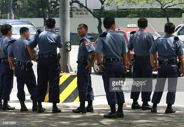 Philippine police patrol the area near the Oakwood condominium 02 August 2003 in the financial district of Makati as part of heightened security...