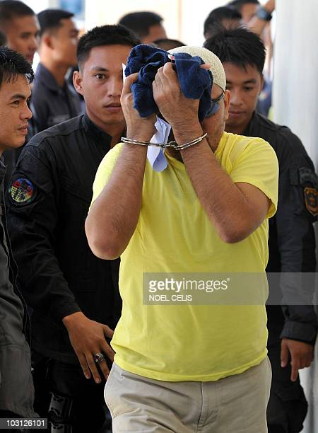 A Philippine policeman accused in the Maguindanao massacre hides his face after the arraignment at a courtroom inside a maximun security prison in...
