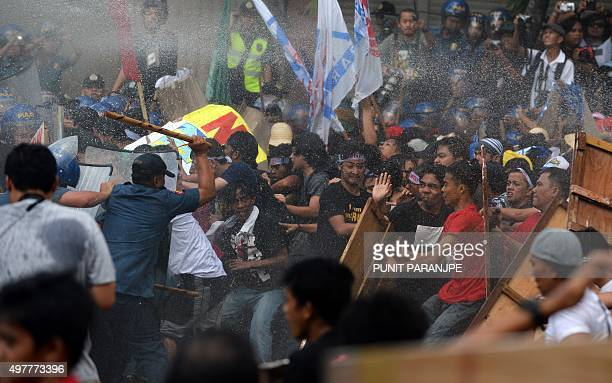 A Philippine policeman clashes with protesters as they are sprayed with water cannon during a demonstration against the AsiaPacific Economic...