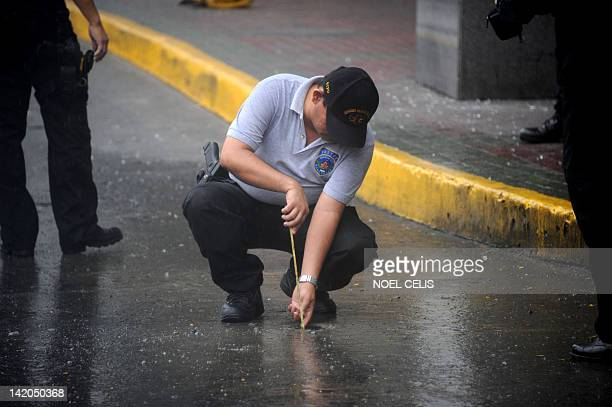A Philippine policeman investigates the area where a grenade exploded after a daylight robbery outside the upperclass Galleria shopping mall in...