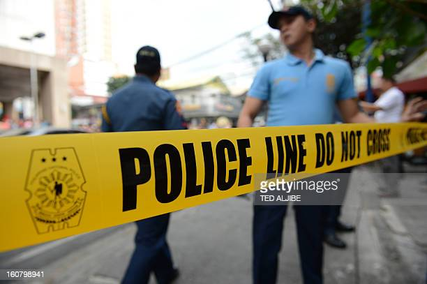 Philippine policemen stand next to a police cordon line during a simulation of a mall robbery in Manila on February 6 as part of heightened security...