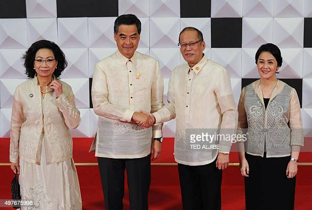 Philippine President Benign Aquino shake hands with Hong Kong Chief Executive Leung Chunying as Aquino's sister Maria Elena Cruz and Leung's wife...