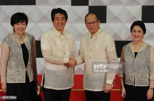 Philippine President Benign Aquino shake hands with Japanese Prime Minister Shinzo Abe as Abe's wife Akie and Aquino's sister Maria Elena Cruz look...