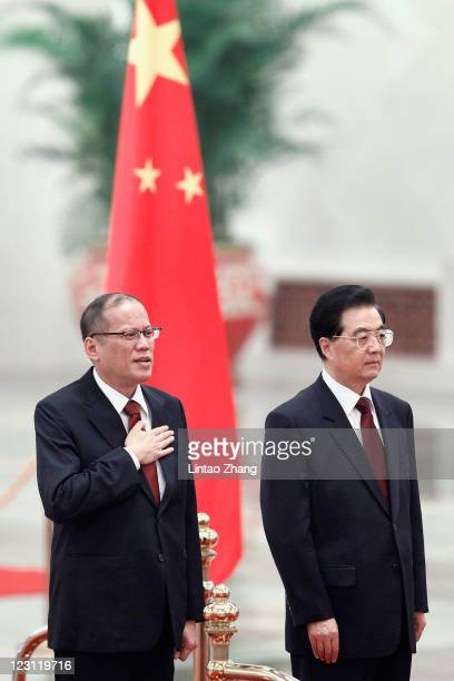 Philippine President Benigno Aquino and Chinese President Hu Jintao listen to the Philippine national anthem during a welcoming ceremony at the Great...