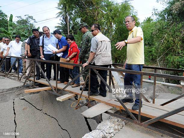 Philippine President Benigno Aquino gestures to photographers as he crosses a makeshift bridge after the concrete bridge collapsed at the height of...