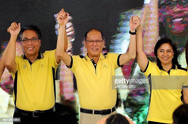 Philippine President Benigno Aquino holds up the hands of Manuel Roxas and Leni Robredo who he has endorsed as presidential and vicepresidential...