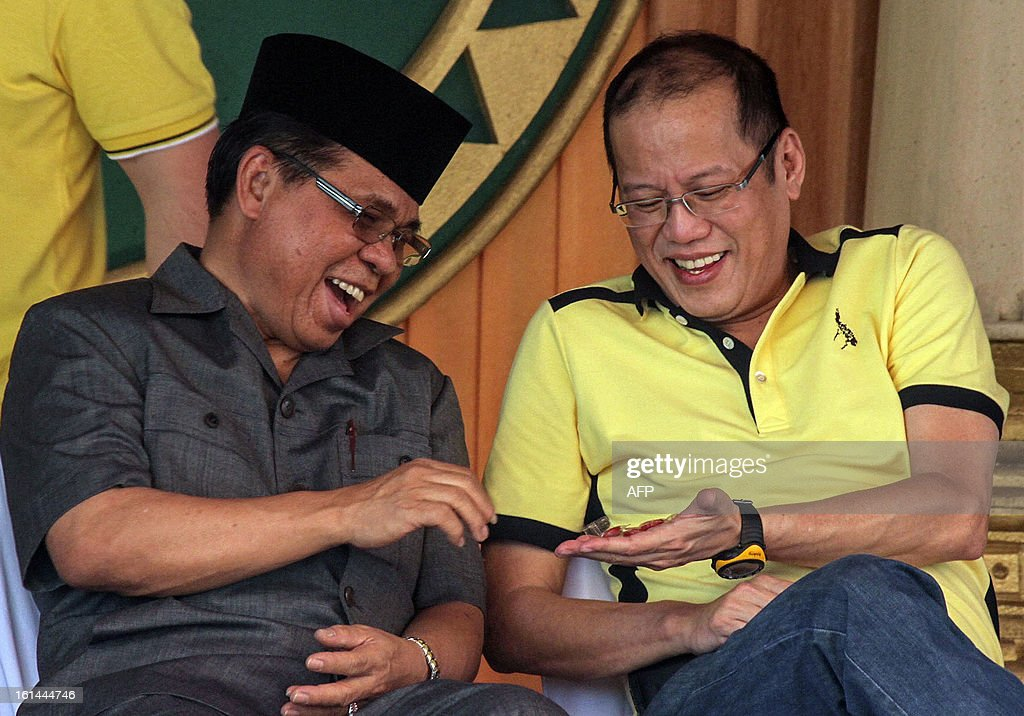 Philippine President Benigno Aquino (R) shares candies with Moro Islamic Liberation Front (MILF) chief Murad Ebrahim during a visit to the rebels stronghold in Sultan Kudarat, in southern island of Mindanao on February 11, 2012. Philippine President Benigno Aquino paid a historic visit February 11 to the stronghold of Muslim rebels and said peace talks with them must be speeded up. AFP PHOTO / Karlos Manlupig