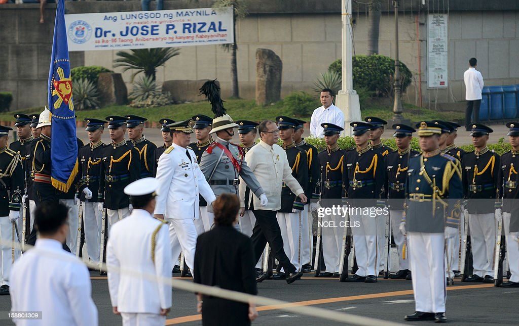 Philippine President Benigno Aquino (C) walks past honour guards during a wreath-laying ceremony on the 106th anniversary of Philippine national hero Jose Rizal at the Luneta Park in Manila on December 30, 2012. Rizal was sentenced to death by a firing squad of the Spanish army after he was accused of leading a revolution against Spain.