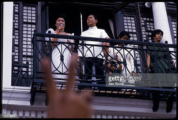 Philippine President Ferdinand Marcos stands by as his wife Imelda sings to supporters from a balcony of the Malacanang Palace in Manila after...