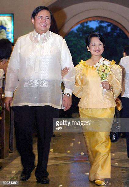 Philippine President Gloria Arroyo accompanied by her husband Jose Miguel Arroyo arrives at the Cebu Metropolitan Cathedral in the central Philippine...