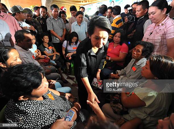 Philippine President Gloria Arroyo condoles with relatives of slain journalists during a visit at the wake in General Santos City south Cotabato...