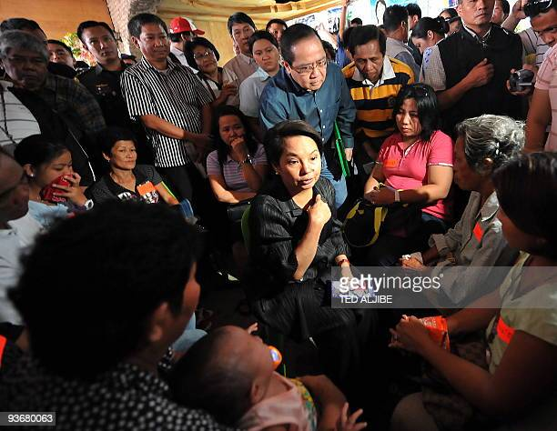 Philippine President Gloria Arroyo holds a dialogue with releatives of slain journalists during a visit at the wake in General Santos City south...