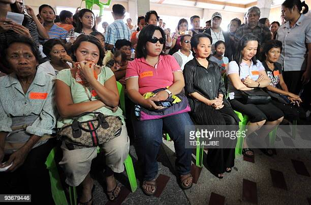 Philippine President Gloria Arroyo sits next to relatives of slain journalists during a visit at the wake in General Santos City south Cotabato...