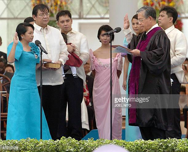 Philippine President Gloria Arroyo takes her oath from Supreme Court Chief Justice Hilario Davide while her husband Jose Miguel Arroyo holds the...
