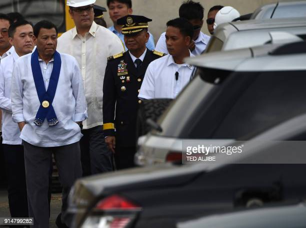 Philippine President Rodrigo Duterte along other government officials inspect luxury vehicles prior to destroying them at a ceremony at the customs...