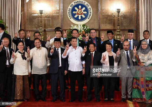 Philippine President Rodrigo Duterte , along with members of government and Moro Islamic Liberation Front peace representatives, gestures with the...