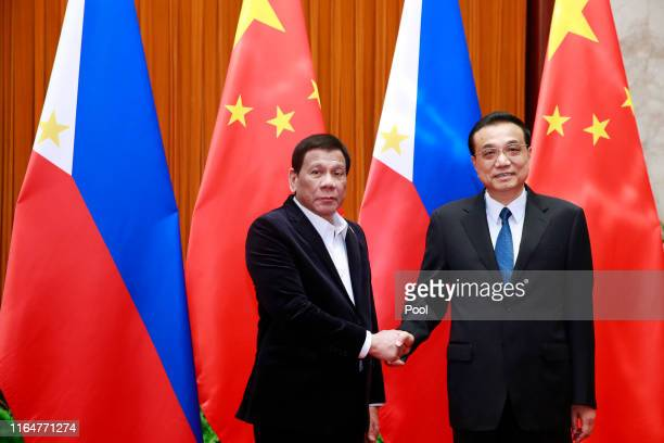 Philippine President Rodrigo Duterte and Chinese Premier Li Keqiang shake hands during their meeting at the Great Hall of the People on August 30,...