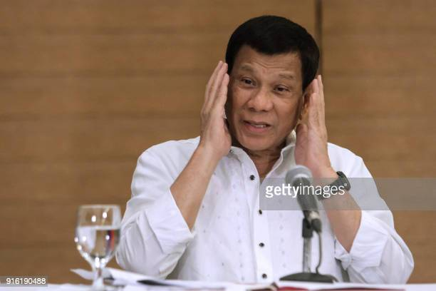 Philippine President Rodrigo Duterte gestures as he speaks during a press conference in Davao City in the southern island of Mindanao on February 9...
