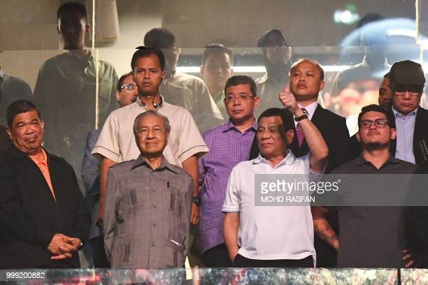 Philippine President Rodrigo Duterte gestures next to Malaysian Prime Minister Mahathir Mohamad after Philippines' Manny Pacquiao beat Argentina's...
