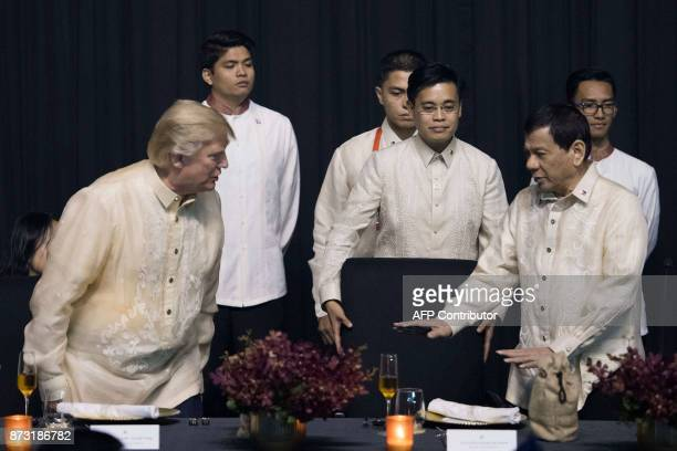 Philippine President Rodrigo Duterte gestures towards US President Donald Trump during a special gala celebration dinner for the Association of...