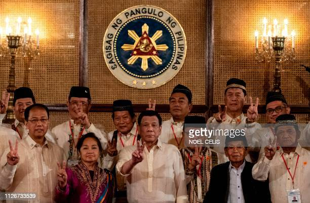 TOPSHOT Philippine President Rodrigo Duterte gives a peace sign with Moro Islamic Liberation Front chairman Murad Ebrahim during the Ceremonial...
