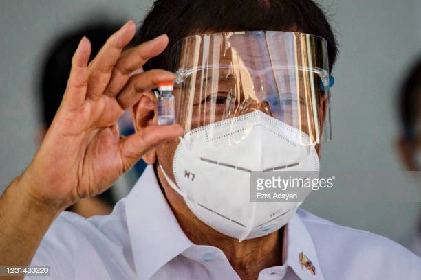 Philippine President Rodrigo Duterte holds up a vial of Sinovac Biotech's COVID-19 vaccines as he witnesses the arrival of a shipment of the vaccines...