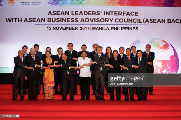 Philippine President Rodrigo Duterte links hands with ASEAN leaders and delegates during the 31st Association of Southeast Asian Nations Summit in...