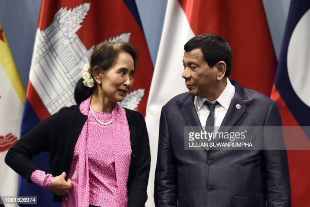 Philippine President Rodrigo Duterte listens to Myanmar State Counsellor Aung San Suu Kyi as they arrive on stage to pose for a group photo before...