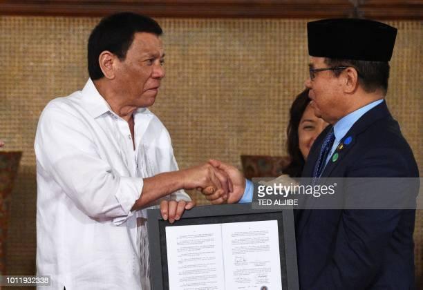 Philippine President Rodrigo Duterte presents the signed document on the Organic Law for Bangsamoro Autonomous Region of Muslim Mindanao to Moro...