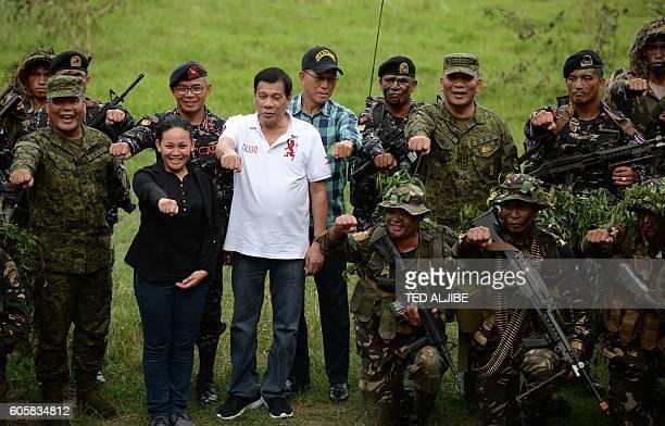 Philippine President Rodrigo Duterte raises a clenched fist with Secretary of Defense Delfin Lorenzana and military chief General Ricardo Visaya as...
