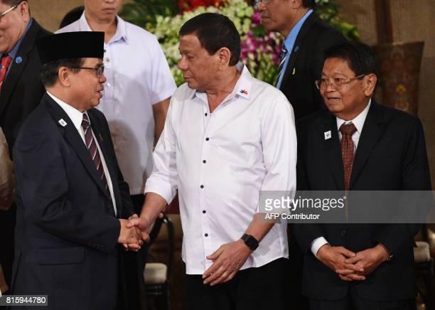 Philippine President Rodrigo Duterte shakes hands with AlHajj Murad chairman of the Moro Islamic Liberation Front as Ghazali Jaafar vice chairman of...