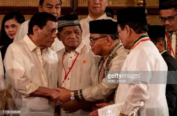 Philippine President Rodrigo Duterte shakes hands with Moro Islamic Liberation Front Chairman Murad Ebrahim during the Ceremonial Confirmation of the...