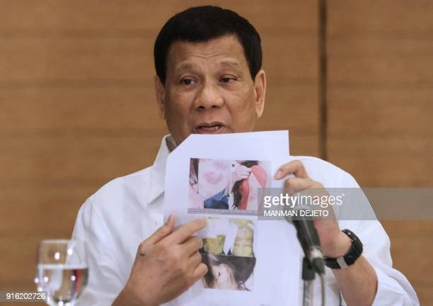 Philippine President Rodrigo Duterte shows a photo of a Filipina worker in Kuwait of whom he said she had been 'roasted like a pig' during a press...