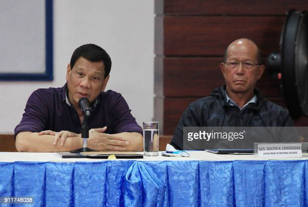 Philippine President Rodrigo Duterte speaks in a meeting with local officials as Defence Secretary Delfin Lorenzana look on during a visit to Legazpi...