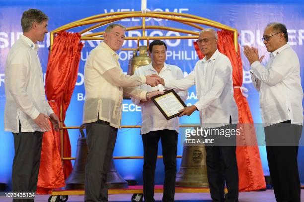 Philippine President Rodrigo Duterte watches as Philippine Defence Secretary Delfin Lorenzana receives a certificate of transfer for three Balangiga...