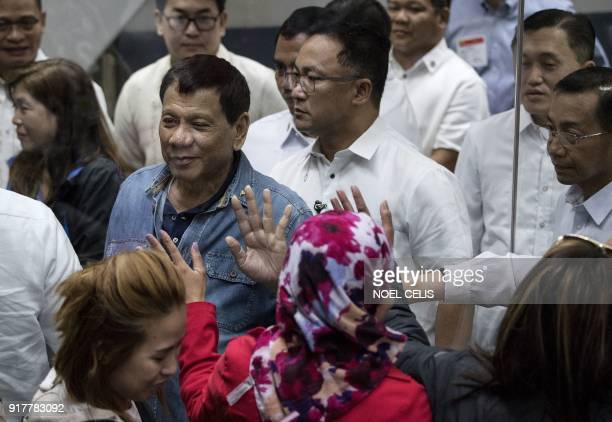 Philippine President Rodrigo Duterte waves through a glass wall to overseas Filipino workers that arrived in Manila from Kuwait at the Manila...