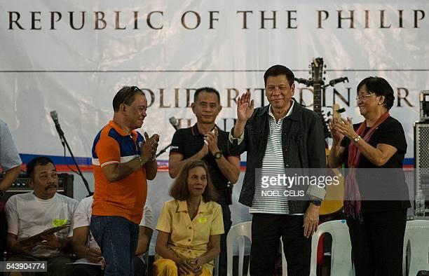 Philippine President Rodrigo Duterte waves to the crowd he visitedcomposed of families living in slum area of Manila on June 30 2016 Authoritarian...