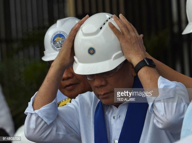 Philippine President Rodrigo Duterte wears a hardhat as he watches the destruction of luxury vehicles at a ceremony at the customs yard in Manila on...